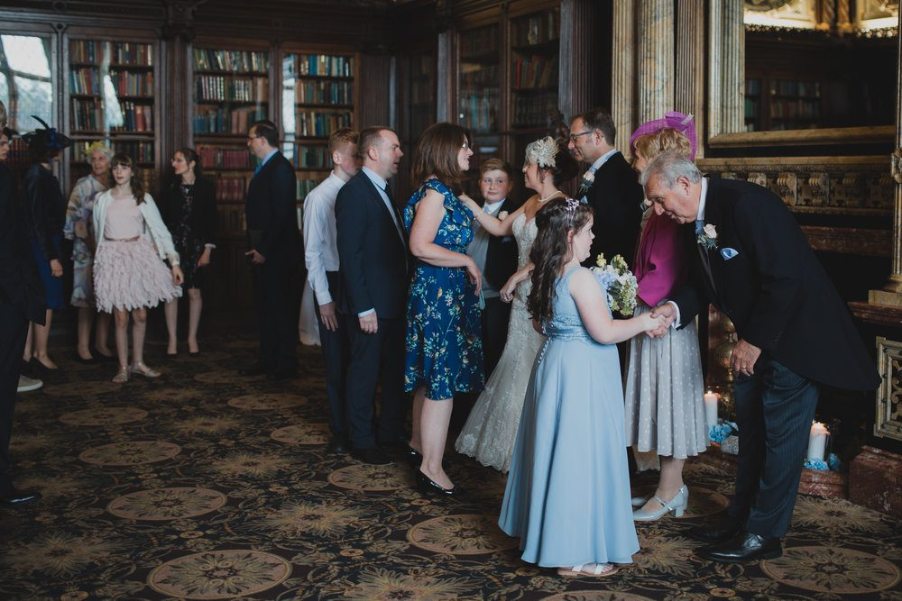 Documentary approach to photographing the receiving line at Crewe Hall in Cheshire. A bridesmaid is welcomed by the groom's father.