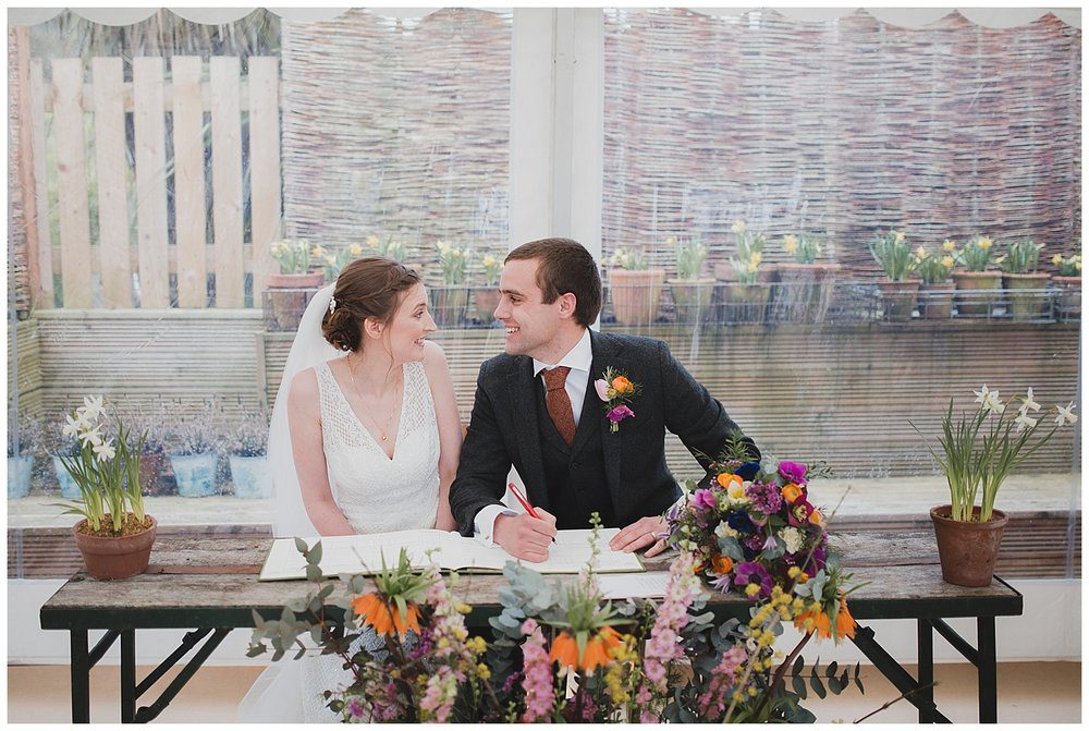 Bride and groom sign the register at their marquee ceremony at the Roebuck inn Mobberley.