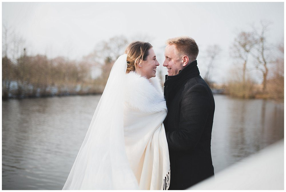 Bride and groom down by the lake at Styal Lodge on their snowy winter wedding day.
