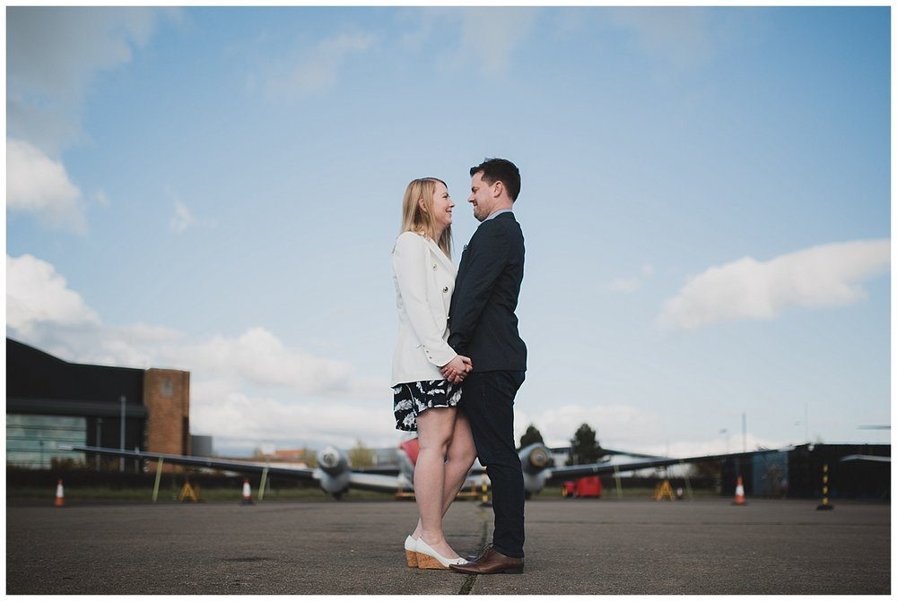 Engaged couple on old runway with plane in the background.