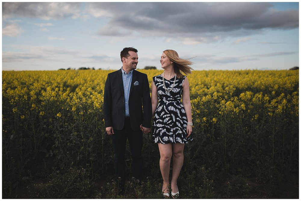 Engaged couple with a field of yellow rapeseed flowers.