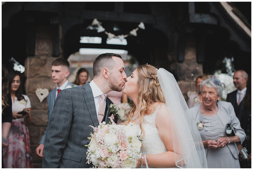 Pastel coloured wedding at Endon Church, Stoke-on-Trent. Bride and groom kiss at the Lych Gate outside this beautiful village church.