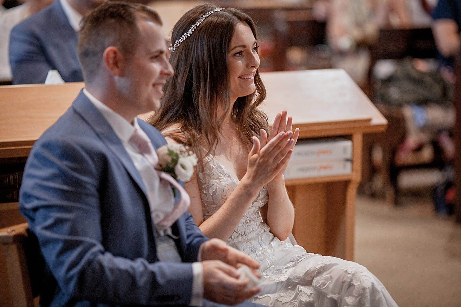 Bride and groom applaude at church wedding