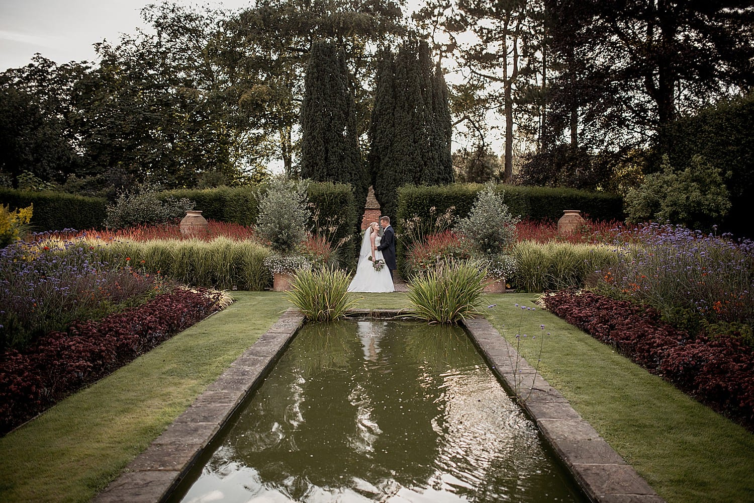 bride and groom near the pond in abbeywood estate gardens