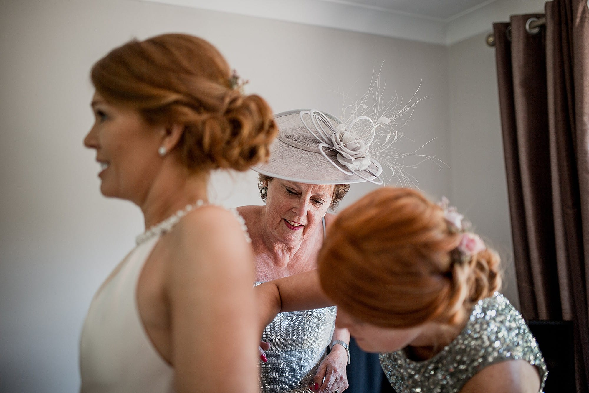 brides mum helps with the dress