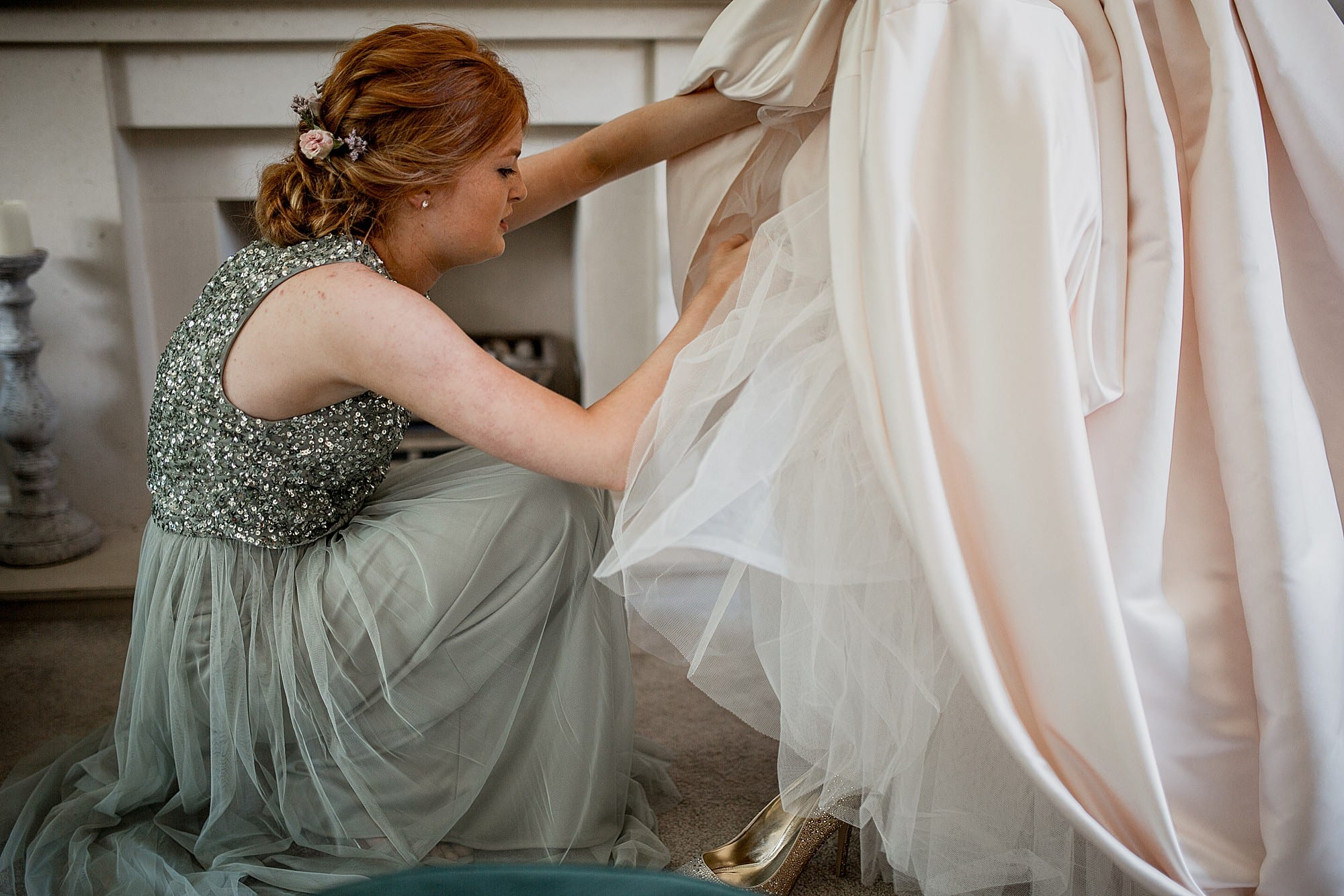 bridesmaid helps the bride with her shoes