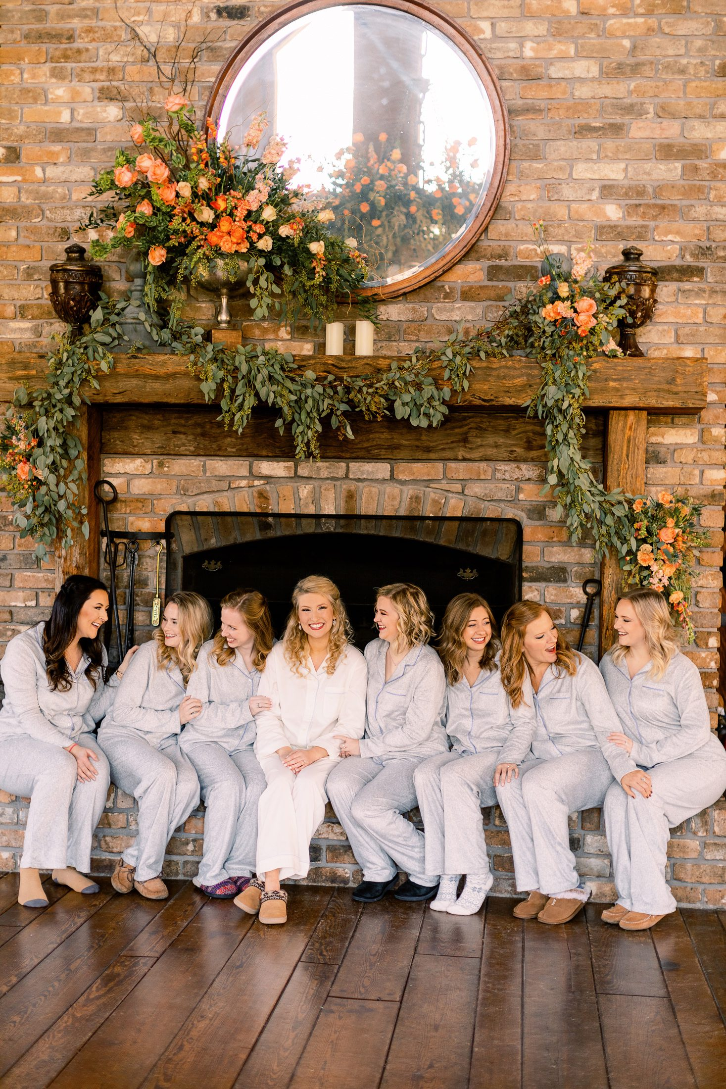Bridesmaids in getting ready attire sitting in front of a fireplace decorated with floral arrangements