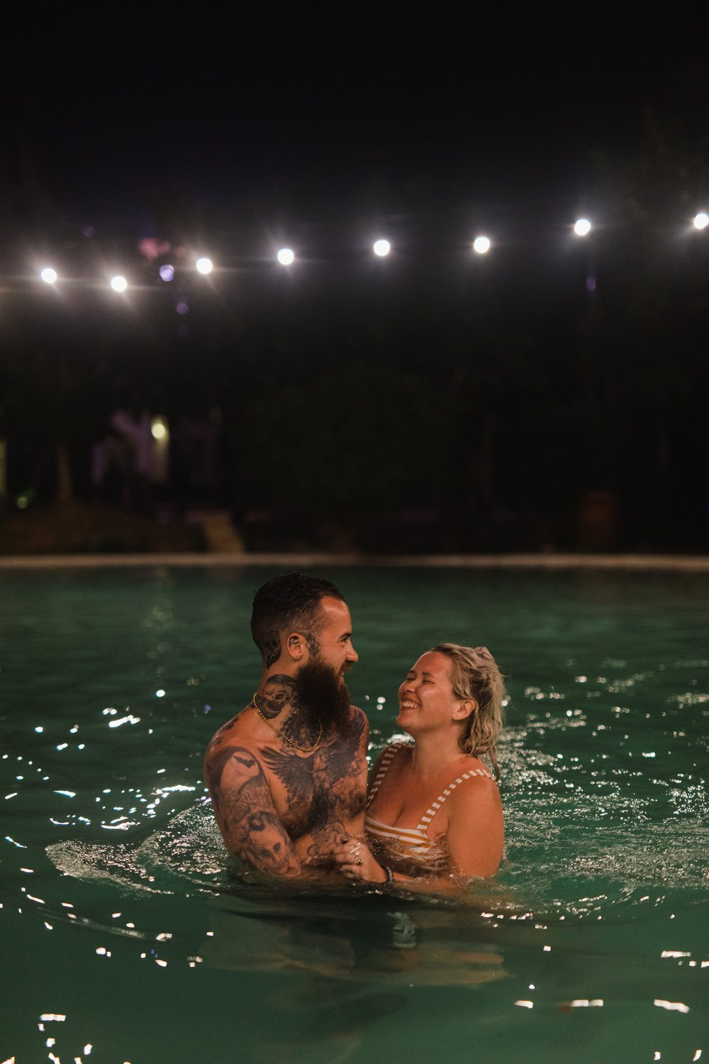 Couple take midnight dip in hotel pool with string lights